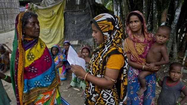 A woman checks for names in the final list of the National Register of Citizens (NRC) on a printed sheet of paper in Pabhokati village in Morigaon district, Assam.(AP File)