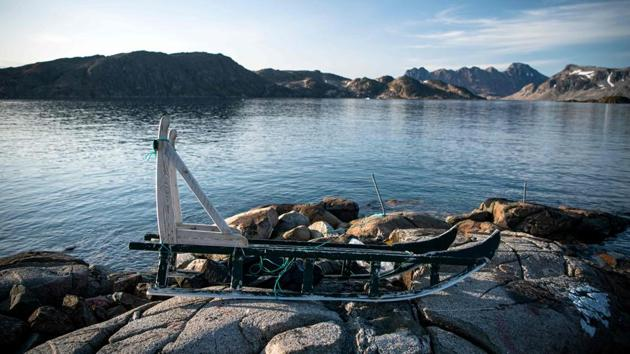 A sled is pictured in Kulusuk, a settlement in the Sermersooq municipality located on the island of the same name on the southeastern shore of Greenland. Kayaking past blue-white icebergs drifting along near a pristine harbour, wandering around colourful houses or trekking in the snow-capped wilderness--July and August are high season for tourists in eastern Greenland. (Jonathan Nackstrand / AFP)