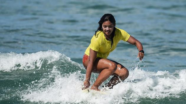 """Nida Soe taking part in a surfing practice session. Paddling hard and smiling, she flung herself up on the board just as a wave was breaking, spreading her arms out for balance before getting knocked off. """"I can't live without surfing,"""" she said. (Ye Aung Thu / AFP)"""