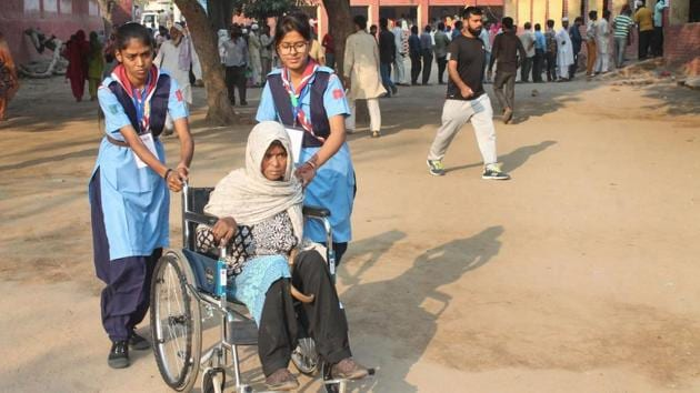 Volunteers assist a differently-abled voter to cast their vote at a polling station at Badkal in Faridabad, Haryana. As many as 1,169 candidates including 105 women of various political parties are contesting the election. Prominent figures include Manohar Lal Khattar, Bhupinder Singh Hooda, JJP's Dushyant Chautala and INLD's Abhay Singh Chautala. (PTI)