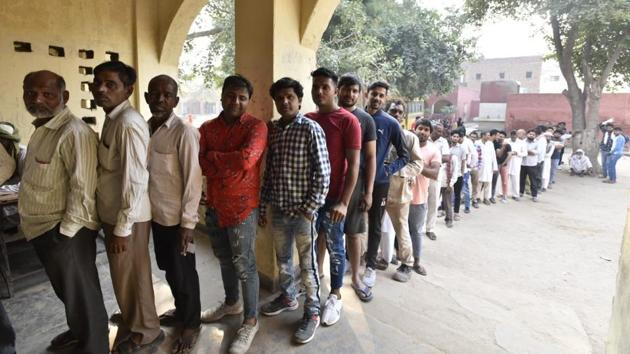 Voters queue up at a polling station, at Badkal Village, in Faridabad, Haryana. Thirty seven per cent of over 1.83 crore voters in Haryana turned out by 2 pm to elect members of the Assembly amidst minor skirmishes and snags in electronic voting machines (EVMs), officials said. (Sanjeev Verma / HT Photo)