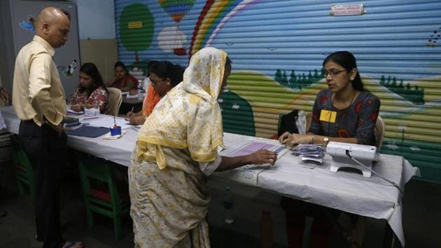 A polling officer explains voting procedure to an elderly woman at a polling station in Mumbai. Voter turnout for Maharashtra stood at 30.89% till 1 pm. Out of the 288 Assembly constituencies in the state, Armori witnessed the highest voter turnout of 52.89% and Ulhasnagar witnessed the lowest at 15.7% till 1 pm. (Rafiq Maqbool / AP )