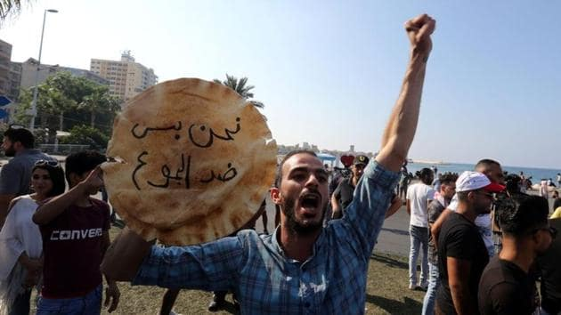 """A demonstrator holds a loaf of bread that read """"we are only against hunger"""" in the southern city of Tyre on Monday. Hundreds of thousands of people have flooded public squares across the country in the largest protests in over 15 years, unifying a public often divided on sectarian lines, in their revolt against status-quo leaders who have ruled for three decades. (Aziz Taher / REUTERS)"""