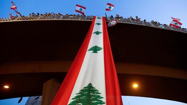 """Demonstrators stand on a bridge decorated with a national flag during an anti-government protest in Jal el-Dib, Lebanon on Monday. Lebanon approved an emergency reform package on Monday in response to protests over dire economic conditions, but the moves did not go far enough to persuade demonstrators to leave the streets as many demonstrators scorned the package as """"empty promises."""" (Mohamed Azakir / REUTERS)"""