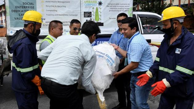 """Nepal Yeti Airlines and Tara Air officials hand over waste collected from the Everest region to Blue Waste to Value workers. """"We received a mix of materials from Everest -- aluminium, glass, plastic, iron -- much of which could be recycled,"""" Maharjan explained, adding: """"We need to up-cycle and add value to them."""" (Prakash Mathema / AFP)"""