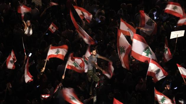Anti-government protesters in Beirut on Monday. The number of protesters swelled following the Cabinet announcement amid intense scepticism that the reforms amounted to anything serious. They included many young men and women as well as whole families, with children waving the national red and white flag with a cedar tree in the centre. (Hassan Ammar / AP)