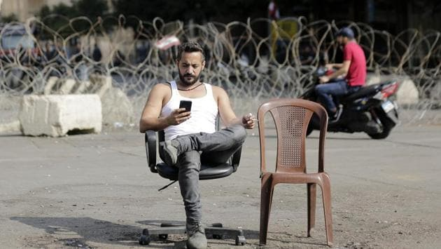 """An anti-government protester checks his phone after spending Sunday night protesting in front of the government palace in Beirut. Following Hariri's speech at the presidential palace, thousands of people gathered outside his office in downtown Beirut chanting: """"The people want to bring down the regime,"""" and """"Revolution, revolution!"""" (Hassan Ammar / AP)"""