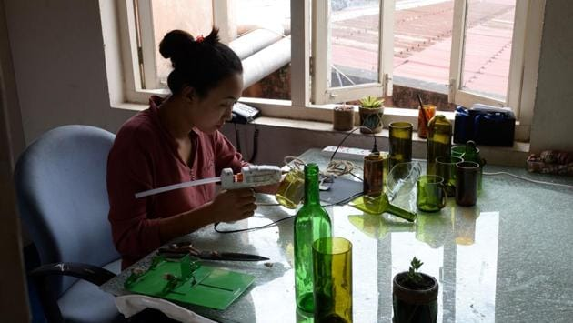 """A worker uses a glue gun as she recycles a bottle. """"When they see these kind of products they are like 'wow', these things can be made and it is possible,"""" Lepcha explained. Their products are now used in upmarket hotels, restaurants, and homes around the capital, and Lepcha says there is growing consumer interest in goods made from salvaged Everest scraps. (Prakash Mathema / AFP)"""