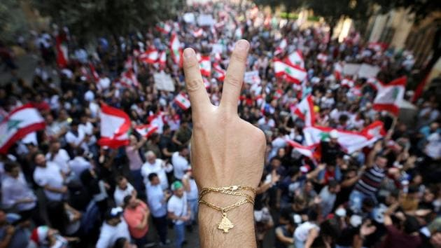 """A demonstrator flashes a V sign during an anti-government protest in downtown Beirut. Layan Ajineh, who came to a protest with her two sons, ages 16 and 12, said that politicians """"have not been able to adopt reforms in 30 years, so how did they come up with them in three days?"""" (Ali Hashisho / REUTERS)"""