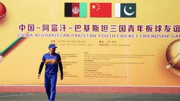 A cricketer walks by a poster of the three-nation event.(HT Photo)