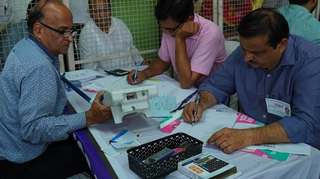 Election official count votes at election counting centre at Government Girls College, Sector 14, in Gurugram on Thursday.(Yogendra Kumar/HT PHOTO)
