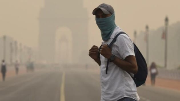 A man covers his face amid dense haze and low visibility at Rajpath, in New Delhi, October 31, 2019.(Burhaan Kinu / HT Photo)