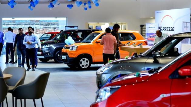 Customers check out car models at Maruti Suzuki Arena Showroom