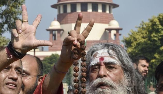 New Delhi: A sadhu flashes the victory sign at the Supreme Court complex after the pronouncement of the Ayodhya case verdict, in New Delhi, Saturday, Nov. 9, 2019. (PTI Photo/Manvender Vashist) (PTI11_9_2019_000067B)(PTI)