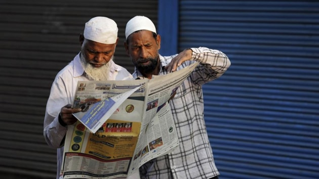 Muslims read about the verdict in a decades-old land title dispute between Muslims and Hindus in a newspaper in Ayodhya on Sunday.(AP Photo)
