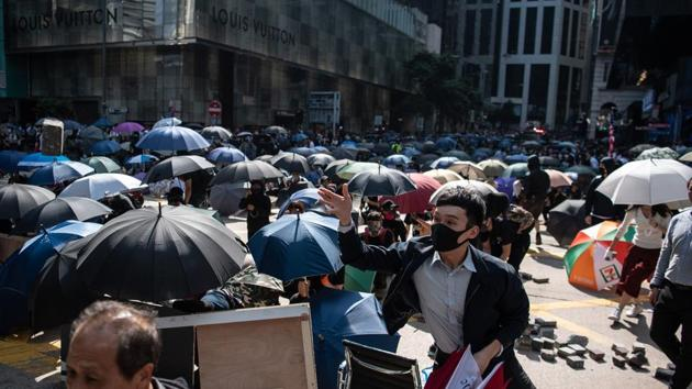 A demonstrator throws a brick on Pedder Street during a lunchtime protest in the Central district of Hong Kong.(Bloomberg photo)