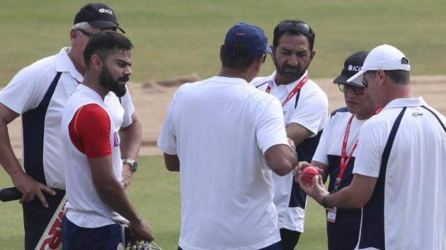 Umpires check out the new pink ball as India's captain Virat Kohli, second left, watches.(AP)