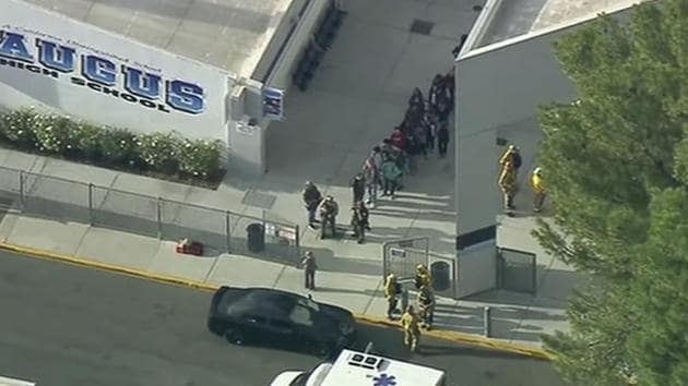 People are lead out of Saugus High School after reports of a shooting on Thursday, Nov. 14, 2019 in Santa Clarita, Calif. The Los Angeles County Sheriff's Department says on Twitter that deputies are responding to the high school about 30 miles (48 kilometers) northwest of downtown Los Angeles. The sheriff's office says a male suspect in black clothing was seen at the school.(AP)