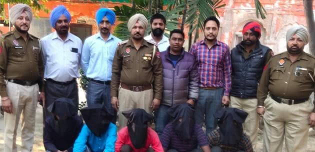 Members of the inter-state gang of robbers (with covered faces) in police custody in Patiala on Monday.(HT PHOTO)