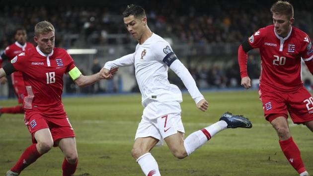 Portugal's Cristiano Ronaldo, center, controls the ball between Luxembourg's Laurent Jans, left, and Luxembourg's Dave Turpel during the Euro 2020 group B qualifying soccer match between Luxembourg and Portugal at the Josy Barthel stadium in Luxembourg, Sunday, Nov. 17, 2019.(AP)