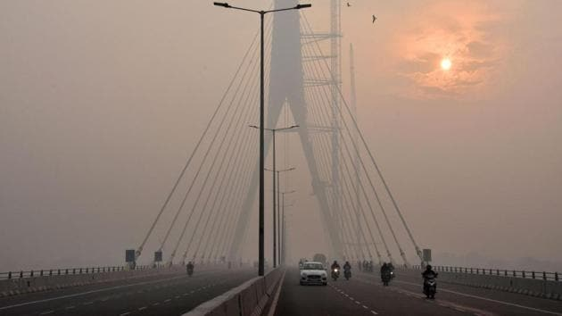 The sun is vaguely seen behind the Signature Bridge amid heavy smog, in New Delhi. The Narendra Modi government deployed 300 field teams to curb pollution after it reached record levels earlier this month, as winds carried smoke from farm stubble burning in areas around New Delhi.(PTI FILE)