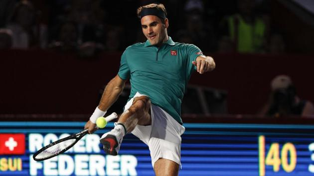 Roger Federer of Switzerland jokes around, juggling a tennis ball with his foot, during an exhibition match.(AP)