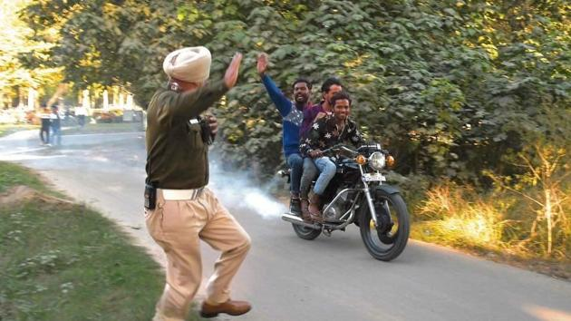 The picture carried by a local daily on Monday of Vikrant and two pillion riders giving the slip to a policeman and tweeted by Chandigarh SSP-traffic Shashank Anand.(Photo courtesy: Chandigarh Traffic Police)