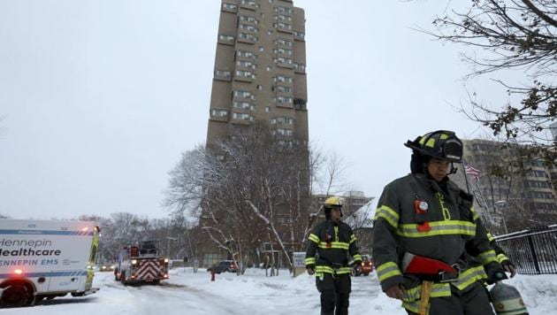 Minneapolis firefighters leave after a deadly fire at a high-rise apartment building, in background(AP)