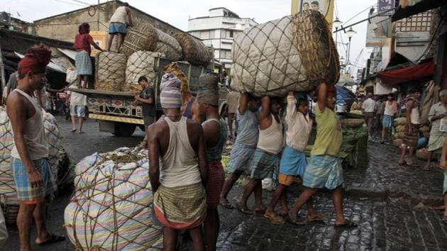 Indian labourers carry a giant basket of vegetables to a wholesale market in Kolkata.(AP)