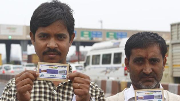 Men hold their FASTags, at the toll office, Jaipur-Delhi side, at Kherki-Daula toll plaza, in Gurugram.(Yogendra Kumar/HT PHOTO)