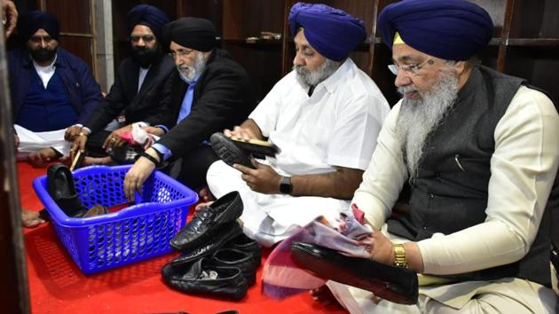 Shiromani Akali Dal president Sukhbir Singh Badal flanked by Shiromani Gurdwara Parbandhak Committee (SGPC) chief Gobind Singh Longowal and former minister Daljit Singh Cheema polishing shoes as(Sameer Sehgal/HT)