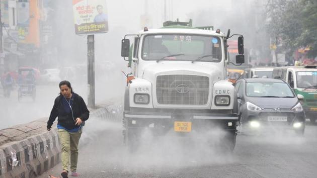 An East Delhi Municipal Corporation (EDMC) water tanker sprinkles water to reduce air pollution while a commuter walks along, at Laxmi Nagar, in New Delhi.(Raj K Raj/HT PHOTO)