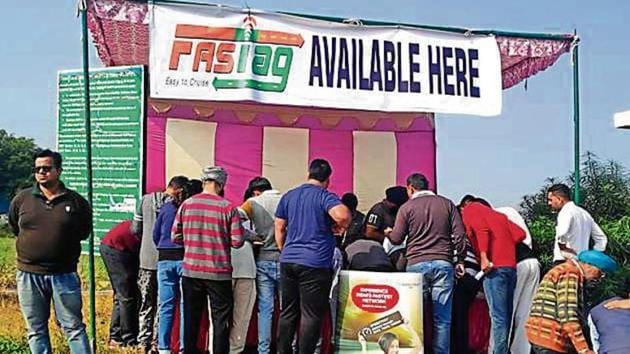 People lined-up to get their Radio-Frequency Identification stickers at Karnal toll plaza.(Neeraj Mohan / HT Photo)