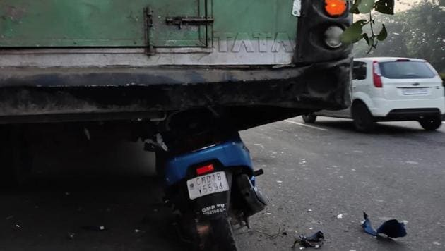 The scooter got stuck beneath the bus after crashing into it from the rear in Sector 29 on Sunday morning.(HT PHOTO)
