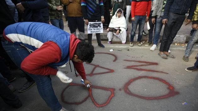A protester paints graffiti on a road, during a protest by students and local residents against the Citizenship Amandment Act (CAA) and National Register of Citizens (NRC), at Jamia Millia Islamia University.(Burhaan Kinu/HT PHOTO)