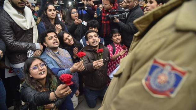 Protestors offer roses to policemen during a demonstration against the Citizenship (Amendment) Act,at Mandi House, New Delhi.(PTI)