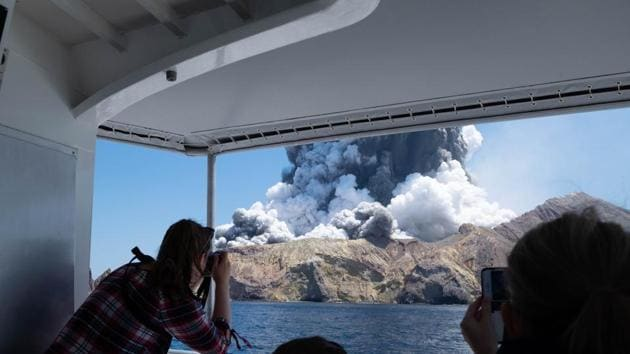 In this Dec. 9, 2019, file photo provided by Michael Schade, tourists on a boat look at the eruption of the volcano on White Island, New Zealand.(AP)