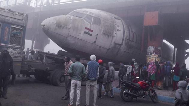 Burdwan: Locals gather after a trailer carrying an old aircraft stuck under an over-brige on the National Highway- 2 at Durgapur in West Bengal on Tuesday morning.(PTI Photo)