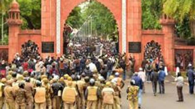 Police personnel stand guard outside Aligarh Muslim University (AMU) as students protest against the passing of Citizenship Amendment Bill.(PTI Photo)
