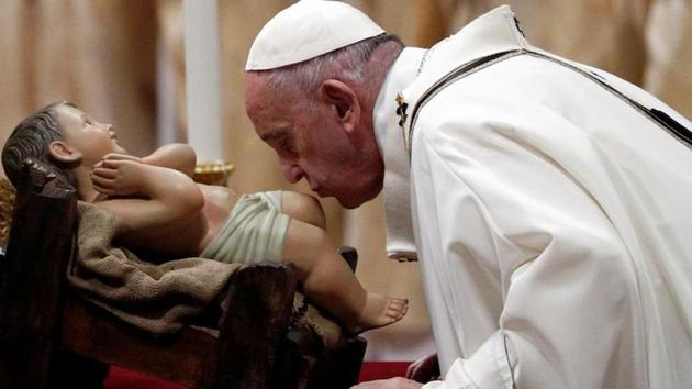Pope Francis kisses a statue of baby Jesus as he leads the Christmas Eve mass in St. Peter's Basilica at the Vatican on December 24.(REUTERS)