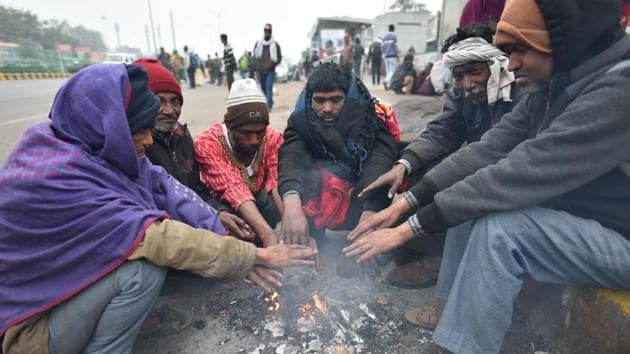 People sit around a bonfire to warm themselves on a cold winter day on December 25, 2019.(Sanchit Khanna/HT PHOTO)