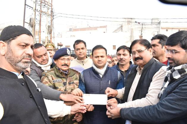 A group of Muslims handing over a demand draft of Rs 627507 to DM Ravindra Kumar and SSP Santosh Kumar Singh in Bulandshahar on Friday against value of damaged property during protests on December 20.(HT Photo)