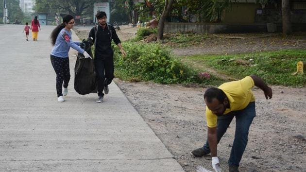 Volunteers of Pune Ploggers collecting garbage at Baner Pashan link road in Pune.(Milind Saurkar/HT Photo)