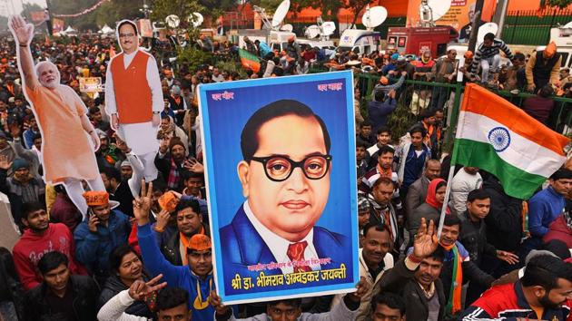 A BJP supporter holds up an image of Dr. BR Ambedkar during Prime Minister Narendra Modi's rally at Ramlila Maidan in New Delhi on December 22.(HT PHOTO)