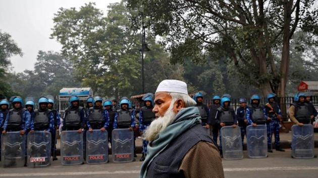 A Muslim man walks past Rapid Action Force personnel during a protest against a new citizenship law, in Delhi.(Photo: Reuters)