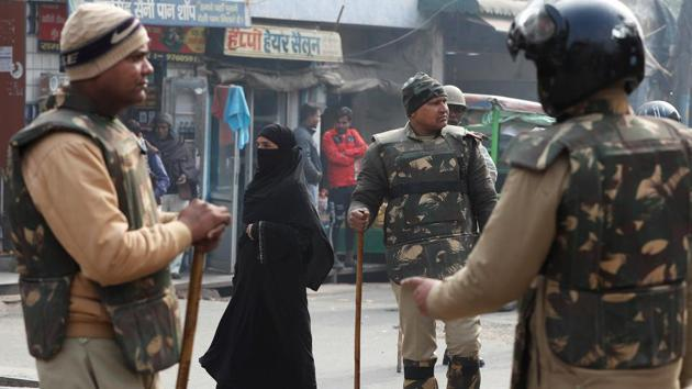 A woman walks past policemen in riot gear on a street in Meerut, Uttar Pradesh. Image used for representational purpose only.(Photo: Reuters)