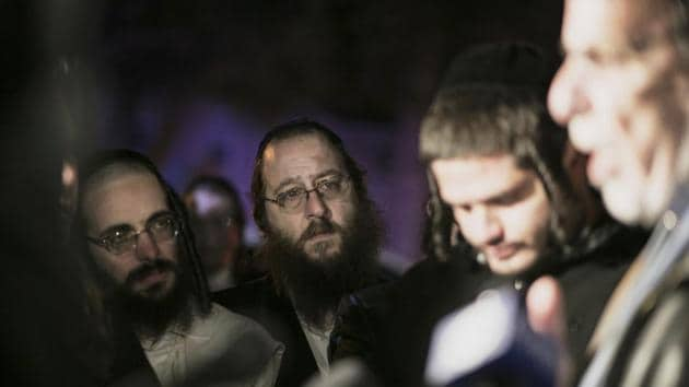 Orthodox Jewish people listen to N.Y. state Assemblyman Dov Hikind speak in Monsey, N.Y., Sunday, Dec. 29, 2019, following a stabbing late Saturday during a Hanukkah celebration. A man attacked the celebration at a rabbi's home north of New York City late Saturday, stabbing and wounding several people before fleeing in a vehicle, police said.(AP)
