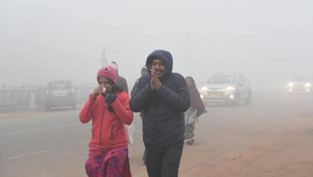 People are seen wearing warm clothes amid dense fog on a cold morning, at Rajpath, New Delhi, on Monday.(Arvind Yadav/HT Photo)