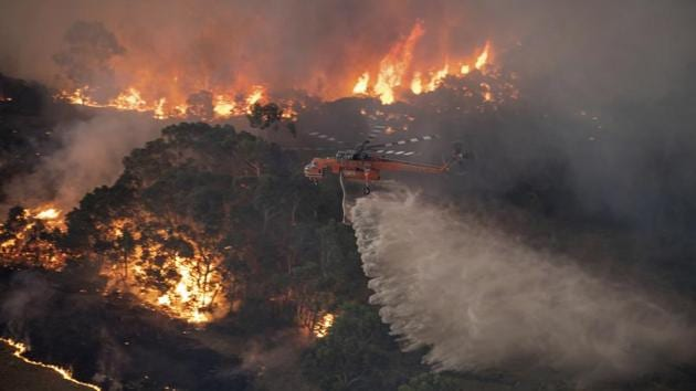 In this Monday, Dec. 30, 2019 photo provided by State Government of Victoria, a helicopter tackles a wildfire in East Gippsland, Victoria state, Australia.(AP)