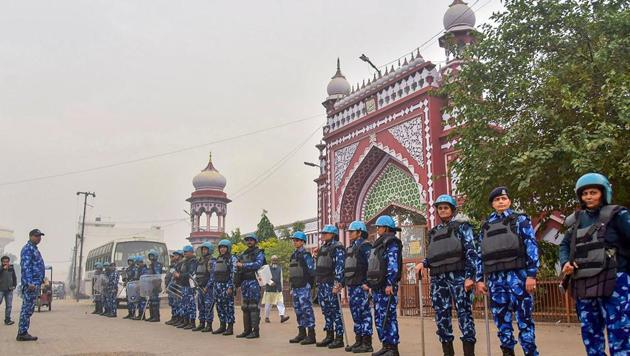 Police personnel stand guard as members of Aligarh Muslim University took out a protest march against CAA in Aligarh.(PTI)